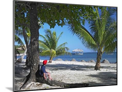 Tourist resting under palm trees on beach at Palmetto Bay, Roatan Island, Honduras-Tim Fitzharris-Mounted Art Print