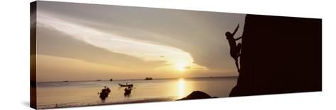 Silhouette of a Man Climbing a Rock, Railay Beach, Krabi, Thailand--Stretched Canvas Print