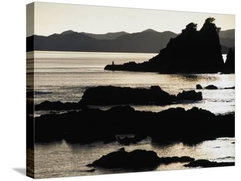 Lone Fisherman on Rocks at Sunrise in Russell, Bay of Islands, Northland, New Zealand-Stephen Saks-Stretched Canvas Print