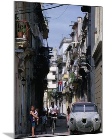 Woman with Baby, Man on Bicycle and Old Car in a Narrow Street Lined with Houses, Havana, Cuba-Rick Gerharter-Mounted Photographic Print