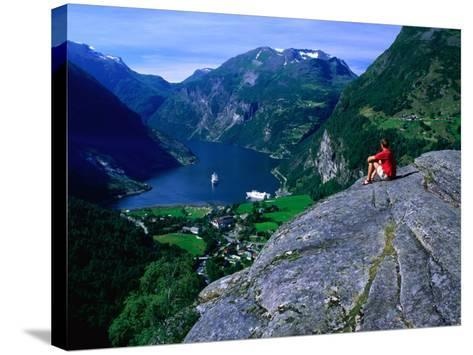 Man Resting on Rock Watching Cruise Ship Sail Out of Geirangerfjord, Geiranger, Norway-Anders Blomqvist-Stretched Canvas Print