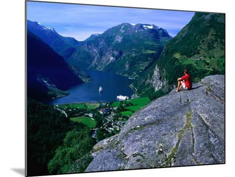 Man Resting on Rock Watching Cruise Ship Sail Out of Geirangerfjord, Geiranger, Norway-Anders Blomqvist-Mounted Photographic Print
