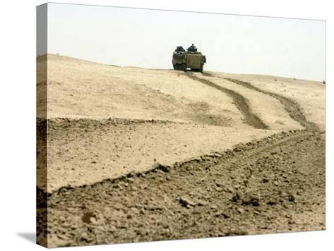 An Amphibious Assault Vehicle Rolls Through a Desert Field North of Fallujah-Stocktrek Images-Stretched Canvas Print