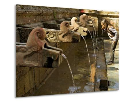 Girl Takes a Drink from the Water Spouts in a Temple Courtyard at Godavari in the Kathmandu Valley-Don Smith-Metal Print