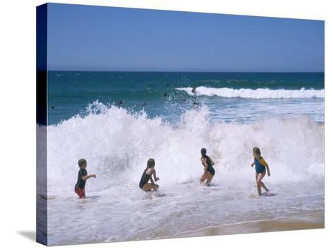 Children Playing in the Surf, Near Gosford, New South Wales, Australia-Ken Wilson-Stretched Canvas Print