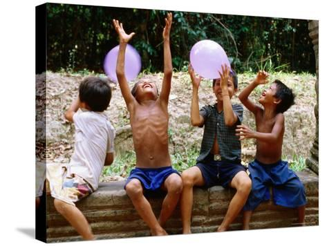 Local Boys Toss Balloons Outside Preah Kahn Temple, Siem Reap, Cambodia-Daniel Boag-Stretched Canvas Print