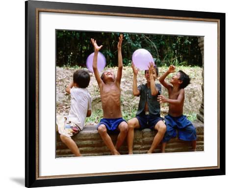 Local Boys Toss Balloons Outside Preah Kahn Temple, Siem Reap, Cambodia-Daniel Boag-Framed Art Print