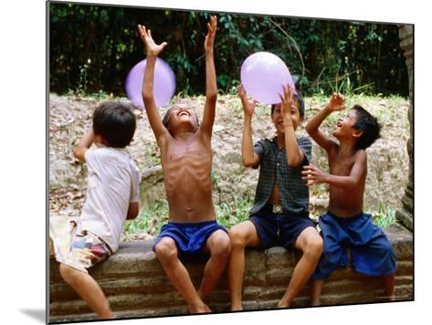 Local Boys Toss Balloons Outside Preah Kahn Temple, Siem Reap, Cambodia-Daniel Boag-Mounted Photographic Print