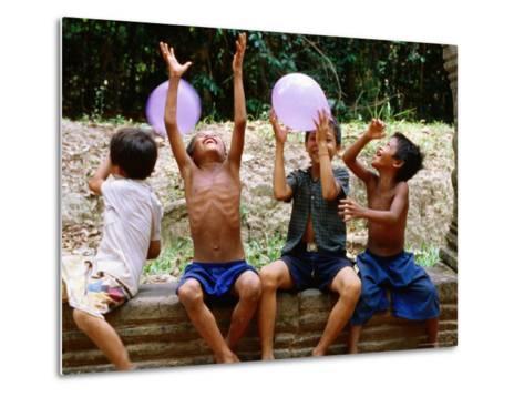 Local Boys Toss Balloons Outside Preah Kahn Temple, Siem Reap, Cambodia-Daniel Boag-Metal Print