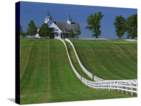 Double White Fence Flows from an Elegant Horse Barn, Woodford County, Kentucky, USA-Dennis Flaherty-Stretched Canvas Print