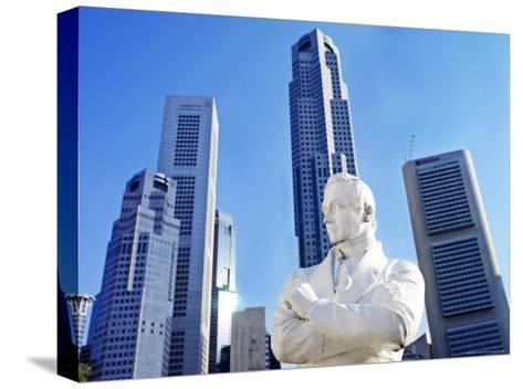 A Statue of Sir Stamford Raffles Against the Cityscape of Singapore-xPacifica-Stretched Canvas Print