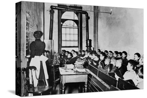 Teacher Instructs Students from Blackboard in Classroom--Stretched Canvas Print