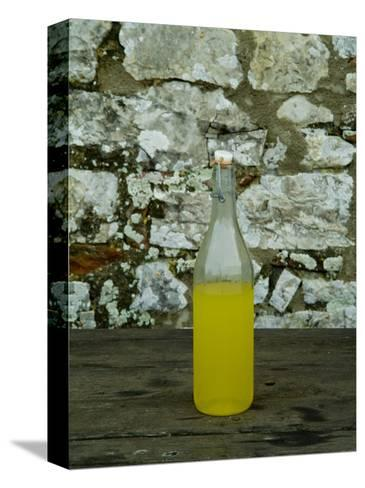 Bottle of Limoncello Sits on a Picnic Table at a Tuscan Villa, Tuscany, Italy-Todd Gipstein-Stretched Canvas Print