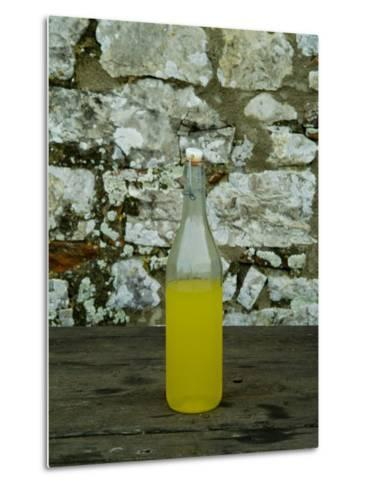 Bottle of Limoncello Sits on a Picnic Table at a Tuscan Villa, Tuscany, Italy-Todd Gipstein-Metal Print