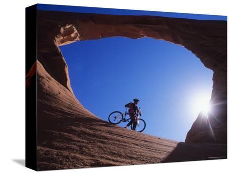 Mountain Biker Stands under an Arch-Bill Hatcher-Stretched Canvas Print