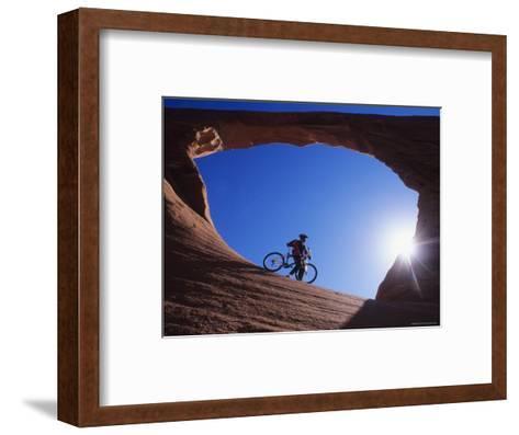 Mountain Biker Stands under an Arch-Bill Hatcher-Framed Art Print