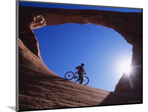 Mountain Biker Stands under an Arch-Bill Hatcher-Mounted Photographic Print