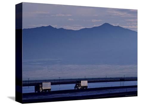 Trucks Along the Highway Next to Great Salt Lake, Utah-Kenneth Garrett-Stretched Canvas Print
