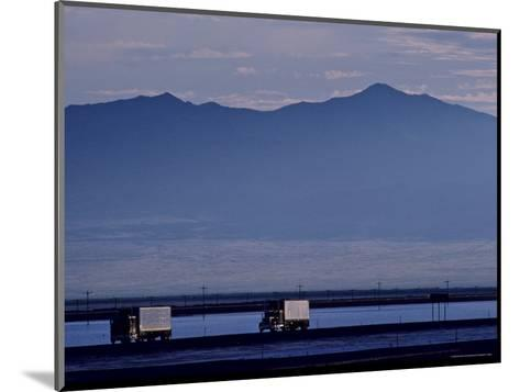 Trucks Along the Highway Next to Great Salt Lake, Utah-Kenneth Garrett-Mounted Photographic Print