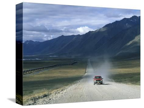 Truck on the Dalton Highway Following the Alyeska Pipeline, Alaska-Rich Reid-Stretched Canvas Print