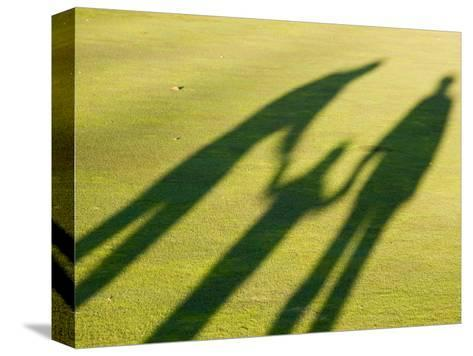 Tall Shadows Loom on the Greens of a Golf Course-Stacy Gold-Stretched Canvas Print