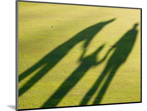 Tall Shadows Loom on the Greens of a Golf Course-Stacy Gold-Mounted Photographic Print