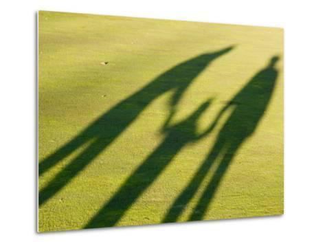 Tall Shadows Loom on the Greens of a Golf Course-Stacy Gold-Metal Print