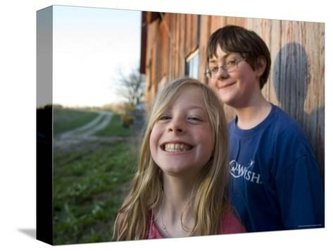 Two Siblings Play near an Old Barn in Nebraska-Joel Sartore-Stretched Canvas Print