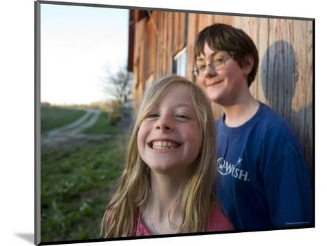 Two Siblings Play near an Old Barn in Nebraska-Joel Sartore-Mounted Photographic Print
