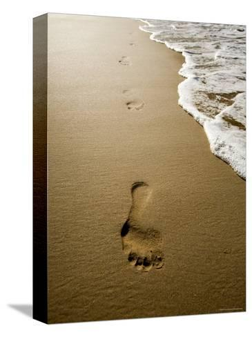 Waves About to Wash over Footprints in the Sand, Anaho Bay, French Polynesia-Tim Laman-Stretched Canvas Print