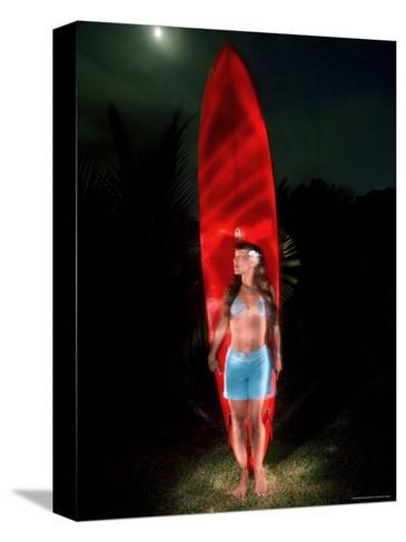 Woman Stands by a Big Wave Surf Board under a Full Moon, Hawaii-Bill Hatcher-Stretched Canvas Print