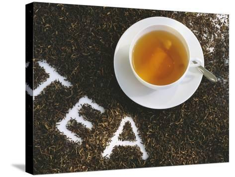Cup of Black Tea, Surrounded by Tea Leaves with the Word Tea--Stretched Canvas Print