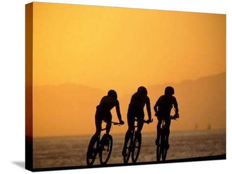 Silhouette of Three Men Riding on the Beach-Mitch Diamond-Stretched Canvas Print