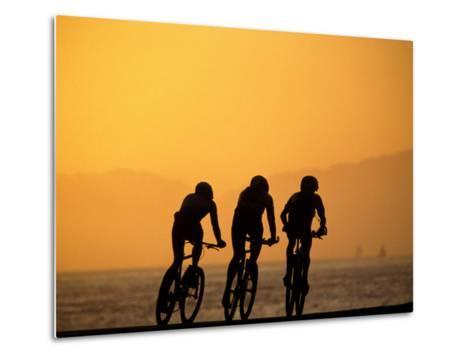 Silhouette of Three Men Riding on the Beach-Mitch Diamond-Metal Print