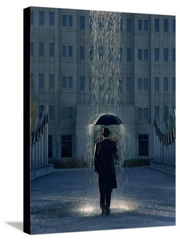 Man with Umbrella Under a Regional Rain-Joseph Hancock-Stretched Canvas Print