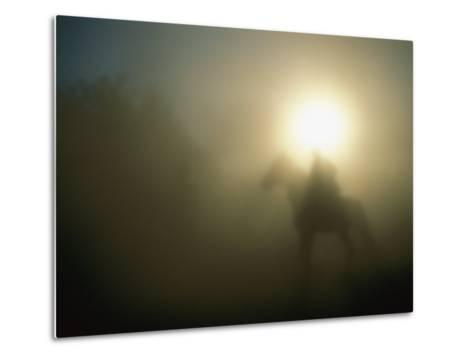 A Person on a Horse is Silhouetted in the Fog-Sisse Brimberg-Metal Print