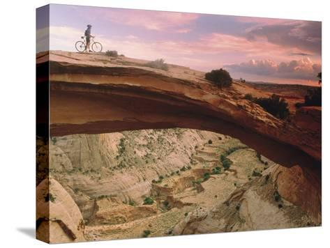 Mountain-Biking over a Natural Arch-Kate Thompson-Stretched Canvas Print