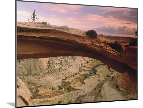 Mountain-Biking over a Natural Arch-Kate Thompson-Mounted Photographic Print