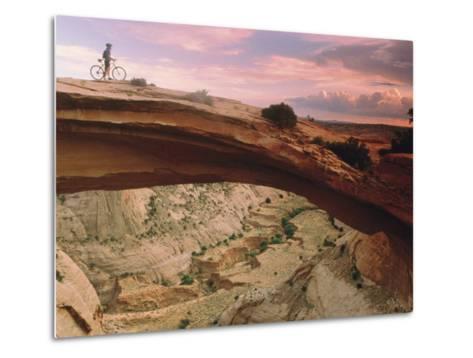 Mountain-Biking over a Natural Arch-Kate Thompson-Metal Print