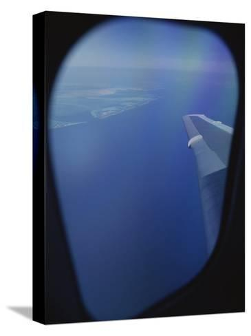 A View out of an Airplane Window over Water and Nearby Islands-Roy Gumpel-Stretched Canvas Print