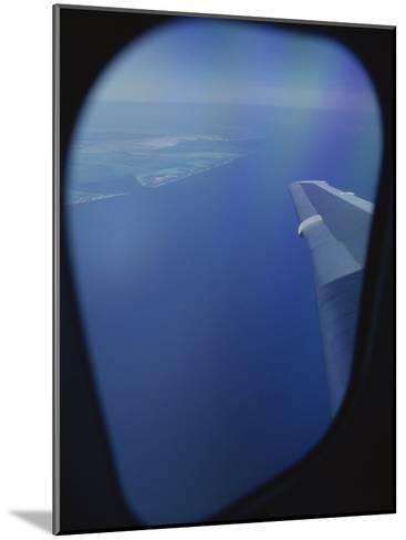 A View out of an Airplane Window over Water and Nearby Islands-Roy Gumpel-Mounted Photographic Print