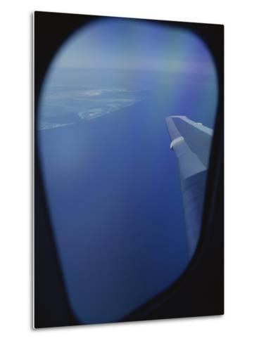 A View out of an Airplane Window over Water and Nearby Islands-Roy Gumpel-Metal Print