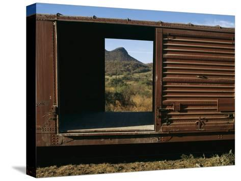 A View of a Distant Hill Through the Door of a Railway Car-Tim Laman-Stretched Canvas Print