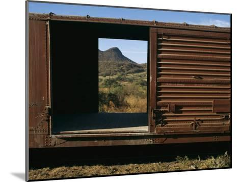 A View of a Distant Hill Through the Door of a Railway Car-Tim Laman-Mounted Photographic Print