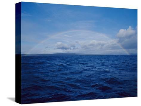 A Rainbow Rises over the Waters Surface in Twofold Bay-Jason Edwards-Stretched Canvas Print