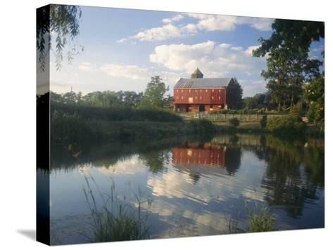 An Old Red Barn Reflected in a Pond-Richard Nowitz-Stretched Canvas Print