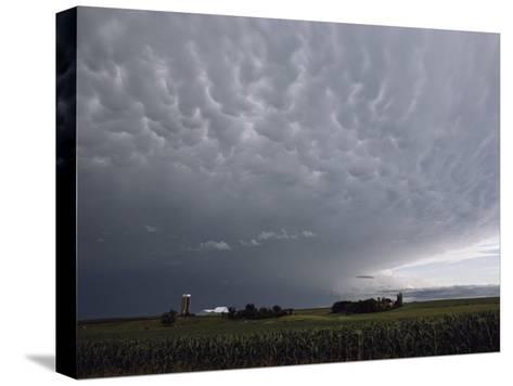 Storm Clouds over a Farm-Annie Griffiths Belt-Stretched Canvas Print