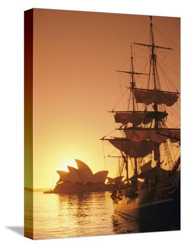 Sydney Opera House and the Hms Bounty, a Replica of the Famous Ship, Silhouetted by the Setting Sun-Richard Nowitz-Stretched Canvas Print