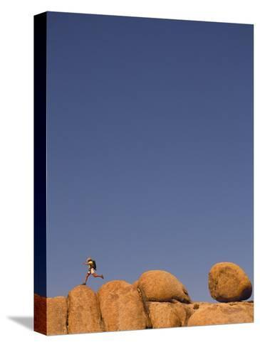 Hiker Jumping on Rocks-Bill Hatcher-Stretched Canvas Print