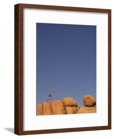 Hiker Jumping on Rocks-Bill Hatcher-Framed Art Print